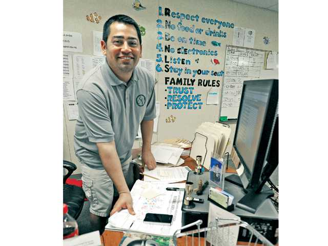 Sierra Vista Junior High School English teacher Robert Isquierdo poses at his desk in his classroom on Friday. Signal photo by Dan Watson.