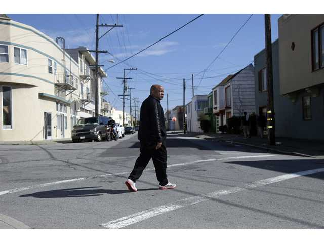 In this Feb. 13 photo, Ernest Morgan walks around his neighborhood, in San Francisco.