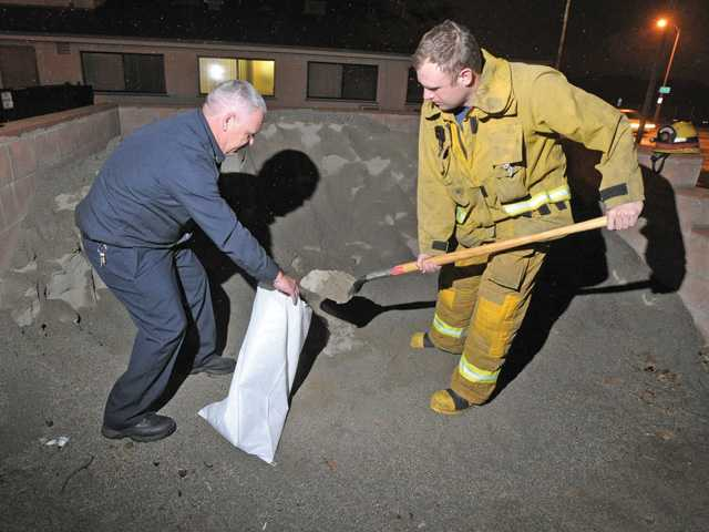 Los Angeles County Fire Captain Ray Nutt, left, and firefighter David Haws fill one of the sandbags available to the public at Fire Station 73 in Newhall Wednesday night. Signal photo by Dan Watson.