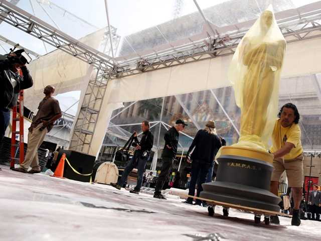Johnny Tamayo pushes an Oscar statue as preparations are made for the 86th Academy Awards to be held at the Dolby Theatre on Sunday, March 2.