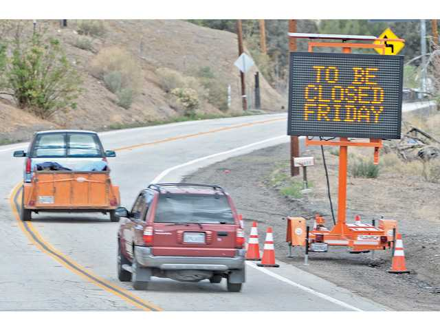 An electronic sign posted on Bouquet Canyon and Vasquez Canyon roads in Santa Clarita on Thursday warns motorists that Bouquet Canyon Road will be closed beginning this morning at 1 a.m. due to the storm. Signal photo by Dan Watson.