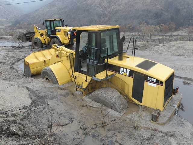 A Caterpillar wheel loader, foreground, stands stuck in about three feet of muck Friday as others work to clear Lake Hughes Road following a massive mud slide. Signal photo by Dan Watson