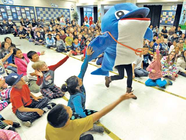 Bridgeport Elementary School mascot, a dolphin named Bubbles, high-fives the students during the Read Across America assembly Friday at the Valencia school. Signal photo by Dan Watson