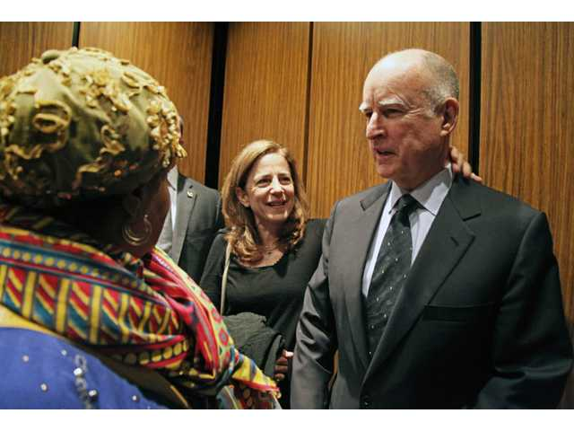 Gov. Jerry Brown, right, with wife Anne Gust Brown, center, talks with Oakland resident Michelle Edwards as they ride the elevator at the Alameda County Registrar's office in Oakland on Friday.