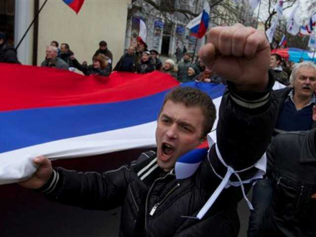 Local residents carry Russian flags and shout slogans rallying over the streets of Crimean capital Simferopol, Ukraine, on Saturday, March 1, 2014.