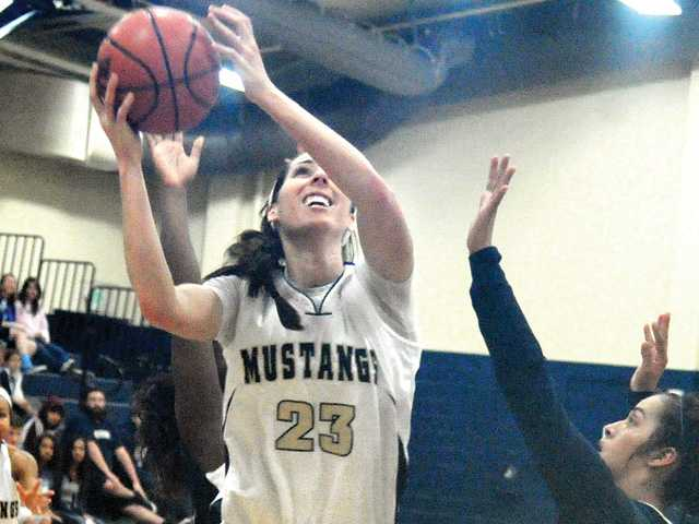 The Master's College's Jacquelyn Marshall (23) shoots against Hope International at TMC on Saturday.
