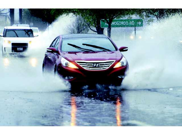 Cars plow through rain water collected on Bouquet Canyon Road near Alamogoro Road on Saturday.