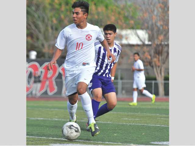 Hart's Brayon Rodriguez drives the ball down the field past Cathedral's Enrique Bustamante at Hart High School.
