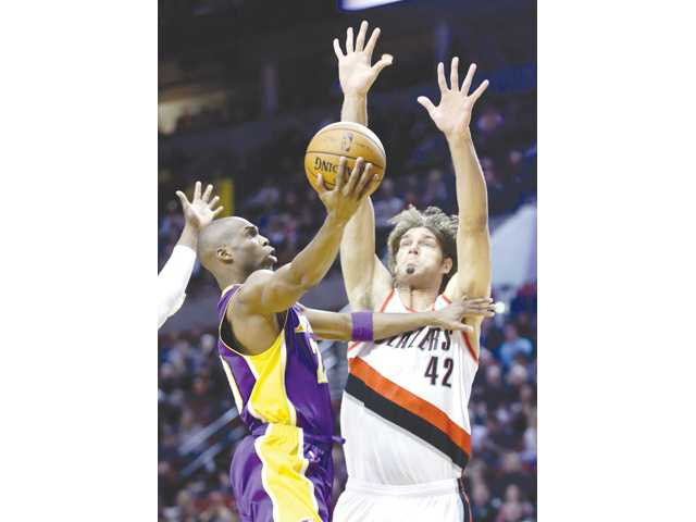 Los Angeles Lakers guard Jodie Meeks, left, goes to the hoop against Portland Trail Blazers center Robin Lopez in Portland, Ore. on Monday.