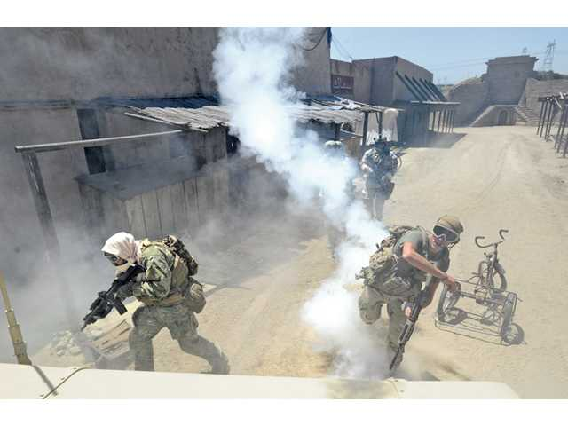 A U.S. Forces team member, right, thows a smoke grenade as his team members advance behind a Humvee during war games on the Middle Eastern town movie set at Blue Cloud Ranch in Saugus.