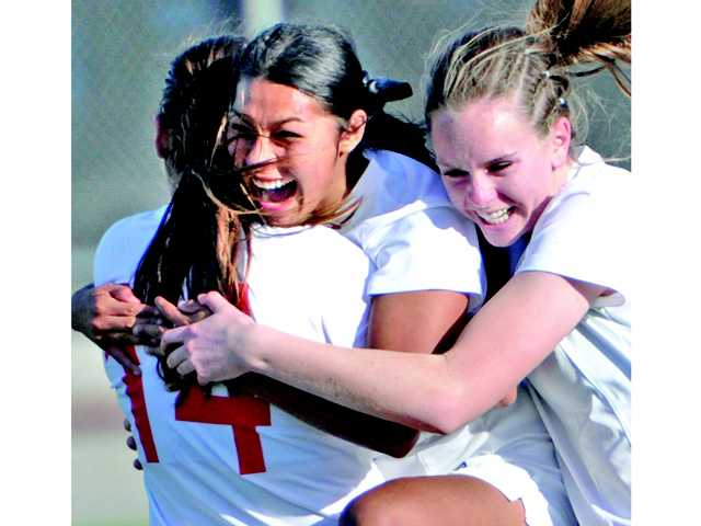 Hart's Jenny Chavez, center, celebrates with teammates Destinney Duron (14) and Sarah Lindborg after she scored the only goal in the CIF-Southern Section Division II semifinals on Tuesday at Hart High School.