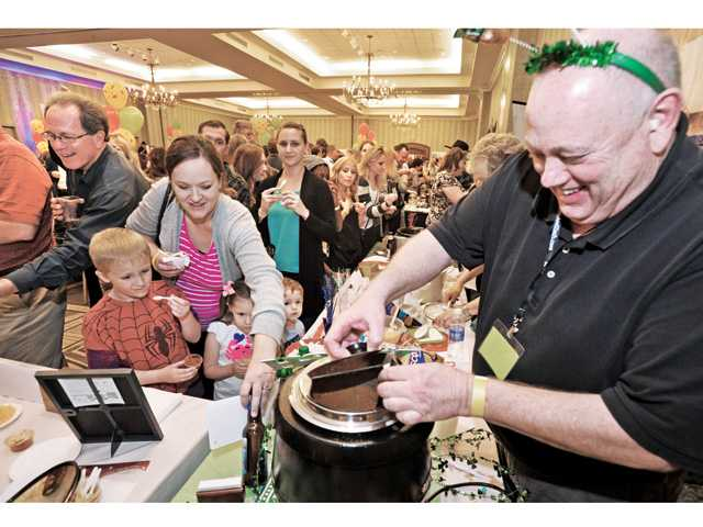 Pastor Brad Brock, right, wearing Irish colors, doles out samples of Pastor Brad's Private Reserve chili to some of the hundreds of attendees who went station to station to sample 44 varieties of homemade chili at the 2nd Annual Charity Chili Cook-Off at the Hyatt Regency Valencia on Wednesday. Signal photo by Dan Watson.