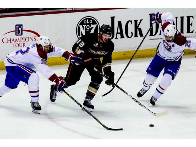 Anaheim Ducks center Nick Bonino, (13), center, dives for the puck against Montreal Canadiens left wing Travis Moen (32) , left, and defenseman Josh Gorges (26) , right, during the first period.