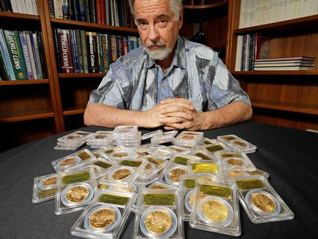 David Halll poses with some of 1,427 Gold-Rush era U.S. gold coins, at his office in Santa Ana. A couple out walking their dog on their property stumbled across the $10 milion in coins.