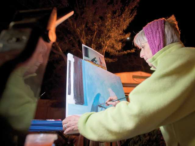 Artist Suzi Kades gives a painting demonstration on Main Street during Thursday night's season opener of the monthly ArtSlam series.Signal photo by Charlie Kaijo.