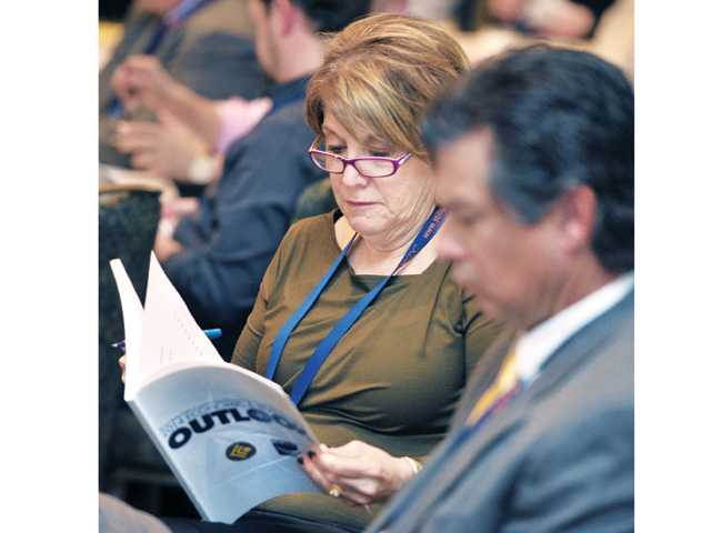 Claudia Bloom from California Institute of the Arts looks through material handed out during Thursday's conference in Valencia.Signal photo by Dan Watson.