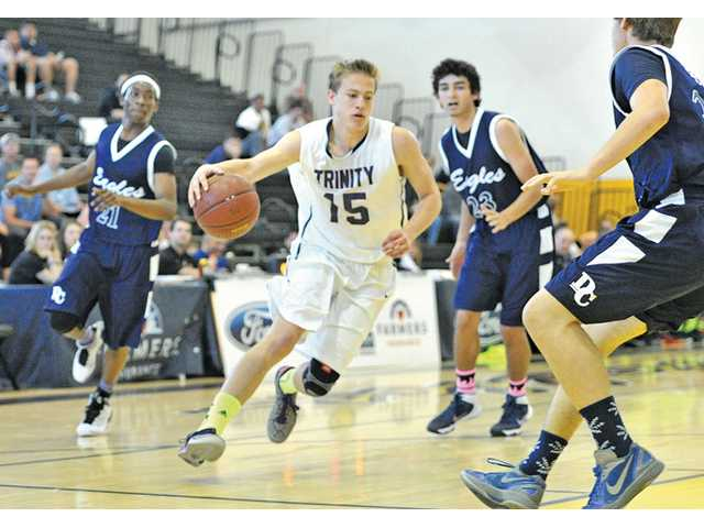 Trinity Classical Academy's Ryan Brooks (15) drives against Desert Chapel defenders on Saturday at Godinez High School.