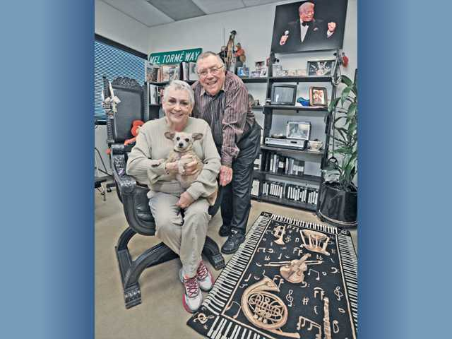Joan and Dale Sheets, along with their rescue dog Itty Bits, pose in their Valencia office with Hollywood memorabilia collected over many years in the industry. Top right is a photo of long-time client Mel Torme and a rug that was a given to them as a gift from pianist Roger Williams. Signal photo by Dan Watson.