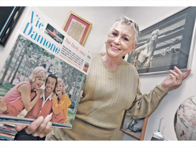 """Joan Sheets displays a record album and photo from when she worked on the 1962 TV series """"The Lively Ones"""" displayed in the Sheets' Valencia office. Signal photo by Dan Watson."""