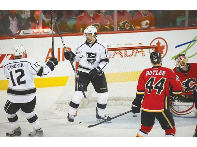 Los Angeles Kings' Justin Williams, center, celebrates his goal with teammate Marian Gaborik, left, against the Calgary Flames in Calgary, Alberta on Monday.