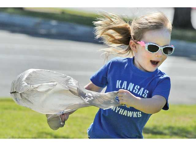 Georgia Doetzi, 3, pretends a plastic bag is her parachute as she runs through Central Park in Saugus on Wednesday afternoon. Signal photo by Dan Watson