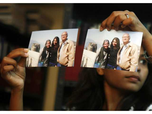 Photographs showing one of the passengers of the missing Malaysian Airlines aircraft Chandrika Sharma, left, her husband Narendran and daughter Meghna, are displayed during a press conference in Chennai, India on Wednesday.