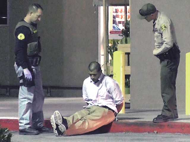 Local deputies stand by one of the suspects arrested in Valencia Wednesday night on suspicion of robbing a Canyon Country hobby shop. Photo byLouie Gallardo -Video Specialtiesfor The Signal.
