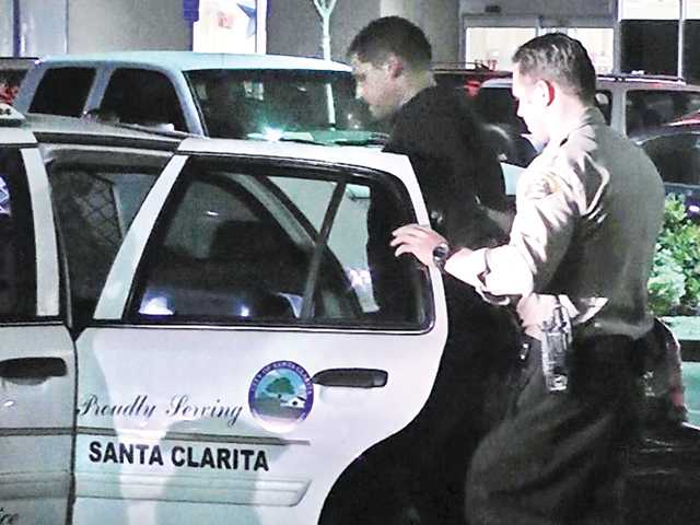 A Santa Clarita Valley sheriff's deputy puts one of the two robbery suspects into a patrol car Wednesday night after arresting them in a Valencia parking lot on suspicion of a Canyon Country robbery. Photo by Louie Gallardo - Video Specialties for The Signal.