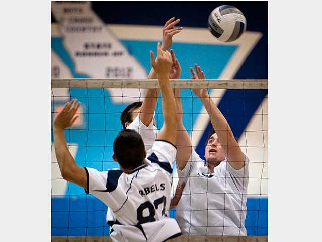 Setter, Justin Coleman, and middle blocker, Clay Roland, go up to challenge the Quartz Hill hitter.