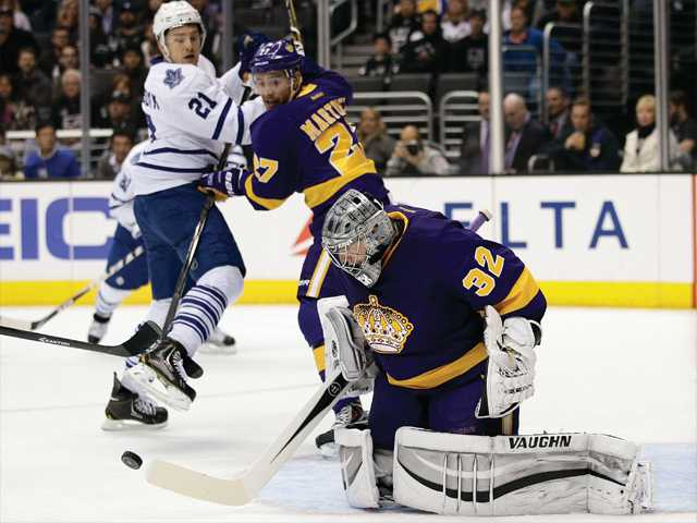 Los Angeles Kings' Jake Muzzin (6) defends Toronto Maple Leafs' James van Riemsdyk (21) as Kings goalie Jonathan Quick (32) watches during the first period on Thursday.
