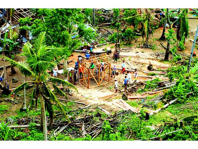 An aerial shot, post-Typhoon Haiyan, of Young Pioneer Disaster Response volunteers and workers reconstructing a building on Bantayan Island in the Philippines. Katlyn Murray/courtesy photo