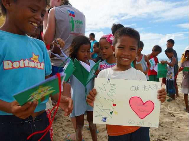 Young Pioneer Disaster Response members with children on the beach in the Philippines after Typhoon Haiyan struck. Katlyn Murray/courtesy photo