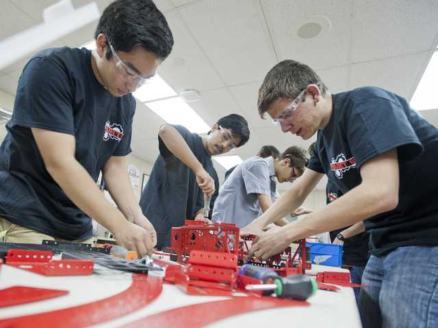 "Members of the Hart School District robotics team assemble a ""shooter"" at West Ranch High School on Friday in preparation for the Los Angeles Regional Robotics Competition on March 22."