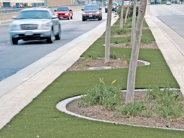 Cars pass by the artificial grass of the center median on Magic Mountain Parkway in Valencia. Photos by Dan Watson.