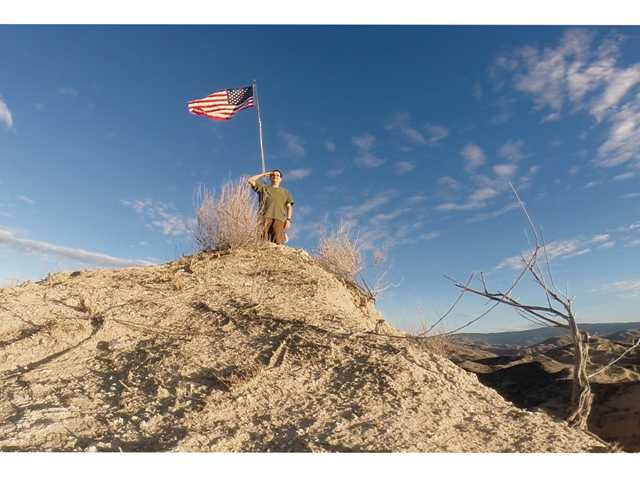 Patrick McGill salutes proudly after raising a new American flag to replace an old, tattered one left on a flagpole atop a hill near his Canyon Country home.