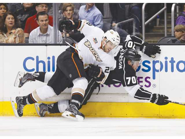 Anaheim Ducks defenseman Mark Fistric, left, checks Los Angeles Kings left wing Tanner Pearson, right, into the boards in Los Angeles on Saturday.
