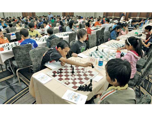 Gio Zanjanipour, center, makes a move on his opponent as 570 Southern California tournament players, ages 5 - 18, competed during the 2014 Super States Chess Tournament Championship held at the Hyatt Regency Valencia on Saturday. Signal photo by Dan Watson.