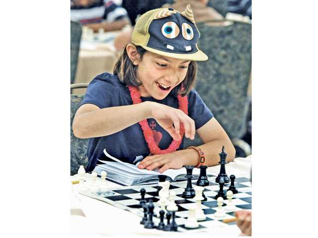 Stephanie Wilson, 10, wears her lucky monster hat as she makes a move on her opponent at the tournament in Valencia on Saturday. Signal photo by Dan Watson.