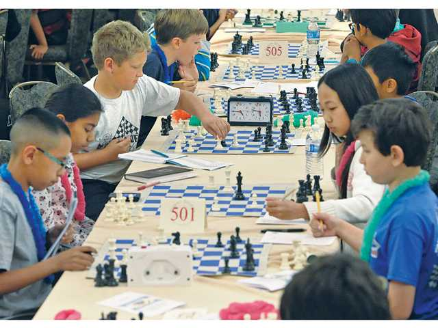 Some of the 570 Southern California tournament chess players, with ages ranging from 5 to 18, compete during the 2014 Super States Scholastic Chess Tournament Championship held at the Hyatt Regency Valencia on Saturday. Signal photo by Dan Watson.