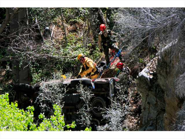 Members of the sheriff's Search and Rescue Team, along with county fire responders, rappel down a ravine to a damaged truck in which one man was killed and another injured after a crash Friday evening north of Castaic. Photo courtesy of Jeff Zimmerman - Zimmerman Media LLC.