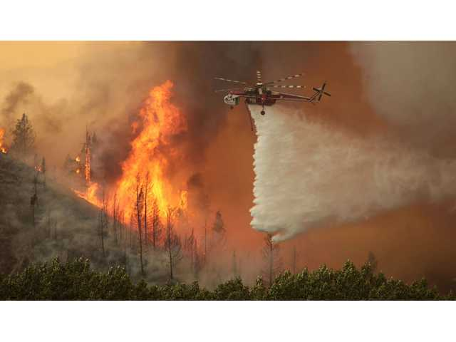 This Aug.,16, 2013 file photo shows helicopters battling the 64,000 acre Beaver Creek Fire north of Hailey, Idaho.