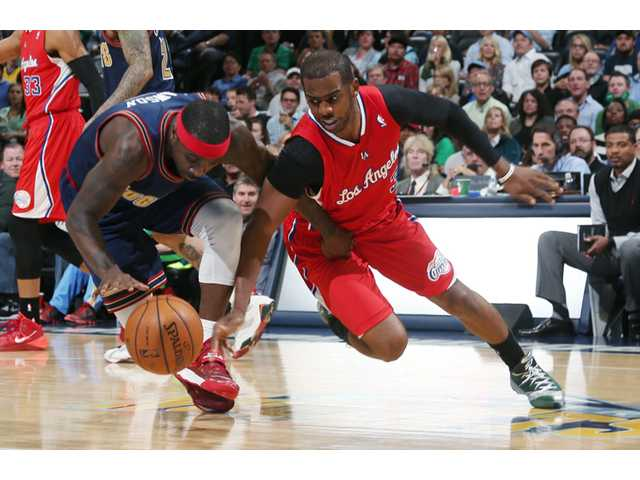 Denver Nuggets guard Ty Lawson, left, pursues a loose ball with Los Angeles Clippers guard Chris Paul on Monday in Denver.