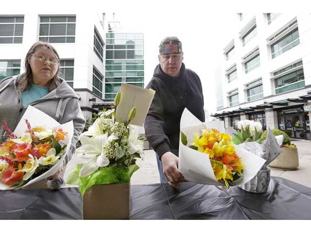 Cindy Quiring, left, and her husband Roger place flowers at a memorial following a helicopter crash Tuesday in Seattle.