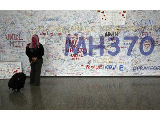 In this March 18 photo, a woman reads messages for passengers aboard a missing Malaysia Airlines plane, at Kuala Lumpur International Airport in Sepang, Malaysia.