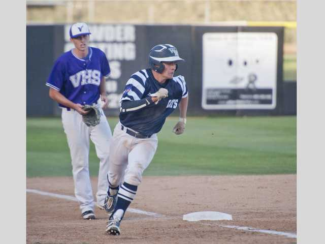 West Ranch's Jake Spurlin, right, runs home past Valencia's Hunter Holland on Wednesday at Valencia High.