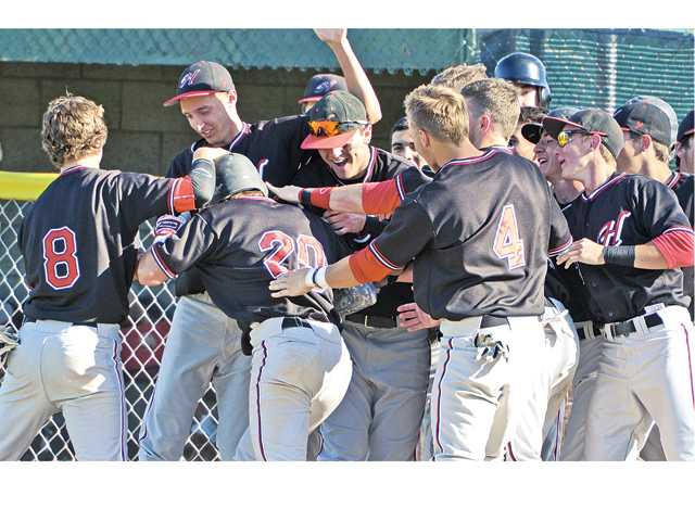 The Hart High baseball team celebrates after Cody Miller (20) hit a go-ahead home run in the sixth inning against Canyon on Wednesday at Canyon High School.