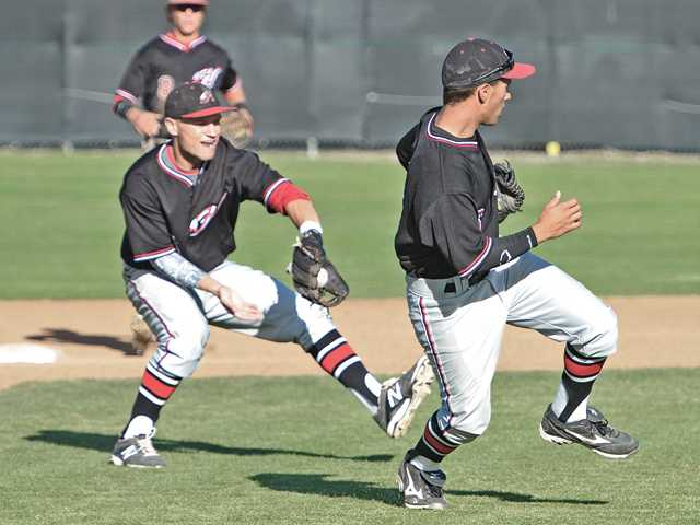 Hart High's Leif Vera, right, veers out of the way so teammate Nick Valaika (4) can play a ground ball against Canyon at Canyon High on Wednesday.