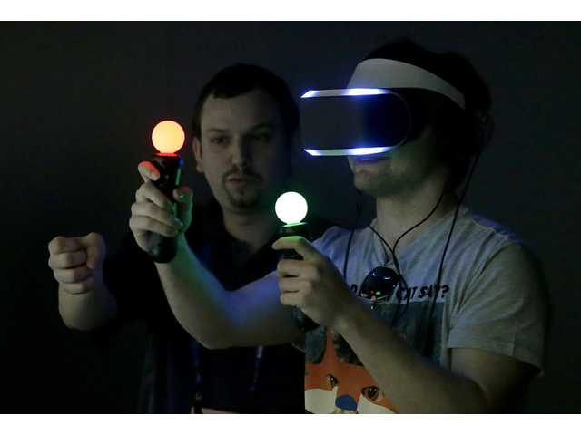 Marcus Ingvarsson, right, tests out the PlayStation 4 virtual reality headset Project Morpheus in a demo area at the Game Developers Conference 2014 in San Francisco on Wednesday.