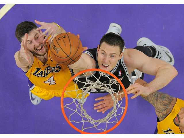 San Antonio Spurs forward Aron Baynes, right, of Australia, reaches for a rebound along with Los Angeles Lakers forward Ryan Kelly during the first half of their game in Los Angeles.