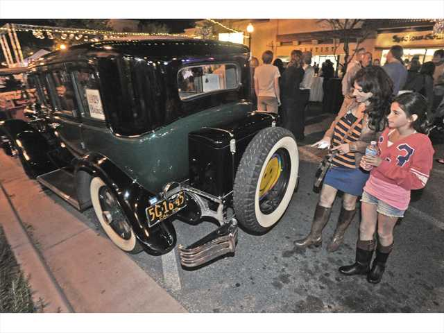 Marla Ferris, left, and Bridgette Mercer, 11, walk past a 1929 Buick sedan on display on Main Street. Signal photo by Dan Watson.